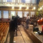 Channel 13's Gina Gaston taping a promo spot on the stage of Vienna's Musikverein